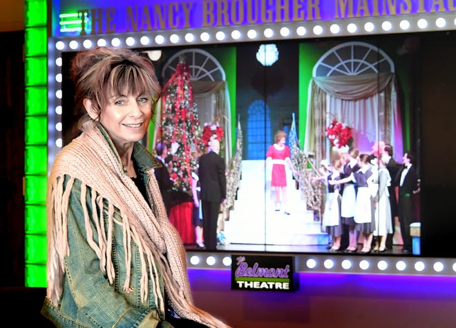 """The Belmont Theatre Executive Director Lyn Bergdol poses with a slide show of the theater's past productions Monday, March 15, 2021. The theater is organizing a two-act virtual showcase called """"From York to New York: A Virtual Youth Vocal Showcase."""" The showcase features current and alumni performers from The Belmont, many of whom have achieved professional theater careers. The first act of the free, streaming series will be available starting March 20, with the second act starting a month later. Bill Kalina photo"""