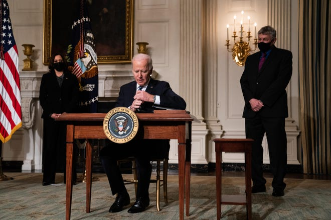 U.S. President Joe Biden signs executive orders after speaking about climate change issues in the State Dining Room of the White House on Jan. 27, 2021, in Washington, D.C. Also pictured, left to right, U.S. Vice President Kamala Harris and White House science adviser Eric Lander. (Anna Moneymaker/Pool/Getty Images/TNS)