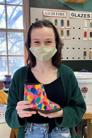 Leon student Ansley Nix shows off her completed ceramic shoe