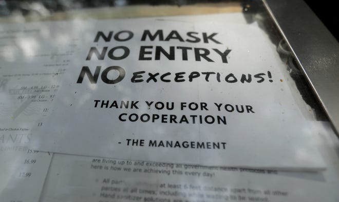 A sign requiring face masks to protect against the spread of COVID-19 is seen at a restaurant on July 7, 2020, in San Antonio, Texas.