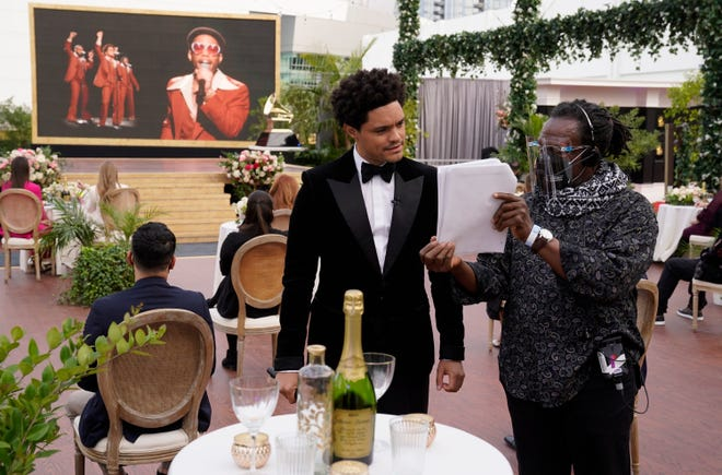 Host Trevor Noah looks over details for the show as Anderson .Paak, right on screen, and Bruno Mars perform.