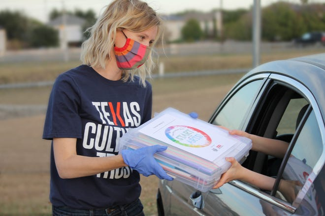 Volunteers hand art boxes to second-graders at Del Valle Elementary School in November.