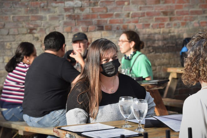 Some customers at 602 Brewing Company in Downtown Bastrop wear masks outside while others don't. Mask wearing inside the establishment is optional.