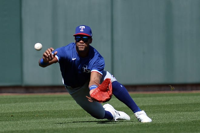 Texas Rangers center fielder Leody Taveras dive for a catch against the Chicago Cubs a spring training game last week. Tavares has struggled at the plate so far this spring.