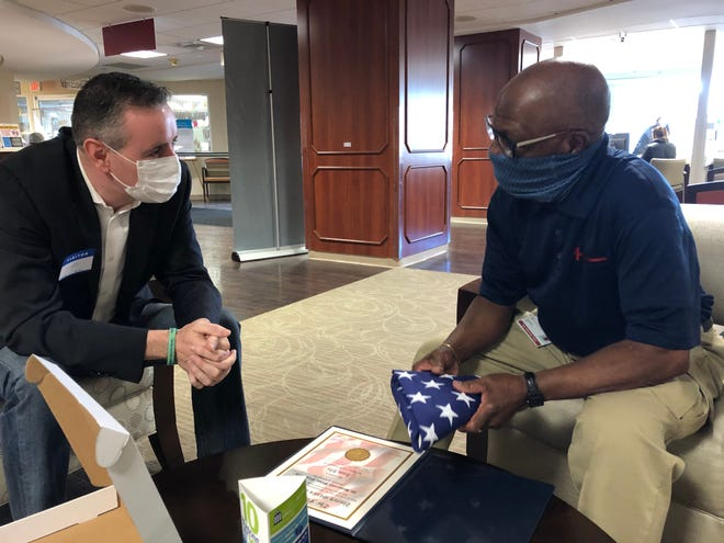 Congressman Brian Fitzpatrick (left) has a conversation with Lower Bucks Hospital floor technician Isaac Irby, to whom he presented an American flag that flew over the U.S. Capitol  to thank Irby for his service to the hospital during the pandemic.