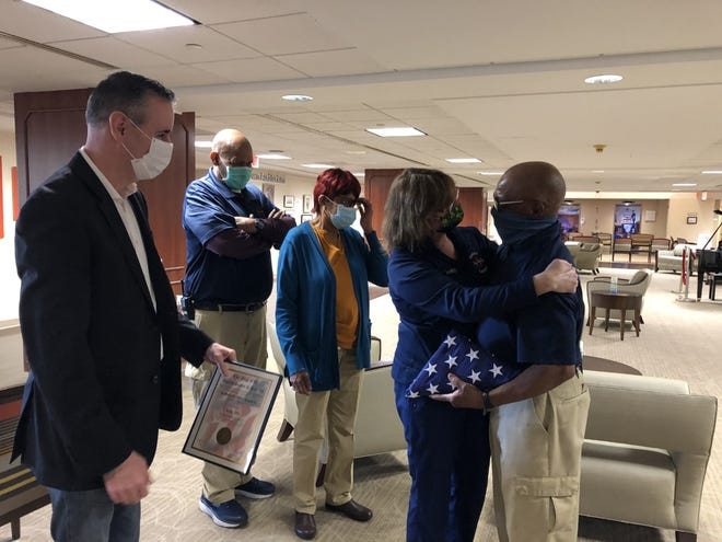 """Lower Bucks Hospital nurse Carol Halner gives a hug to Isaac """"Ike"""" Irby as Congressman Brian Fitzpatrick prepares to hand him a commendation along with the flag he received and the hospital's  Environmental Service staff members Ricky Winton and Delois Wilson wait to congratulate Irby."""