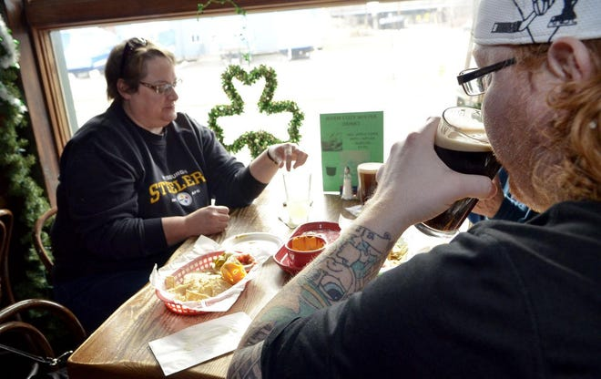 Jason Foley of Beaver has a Guinness with friends, Wendy Frum of New Galilee and Susan Oettle of New Brighton, ain 2015 at Kelly's Riverside Saloon in Bridgewater