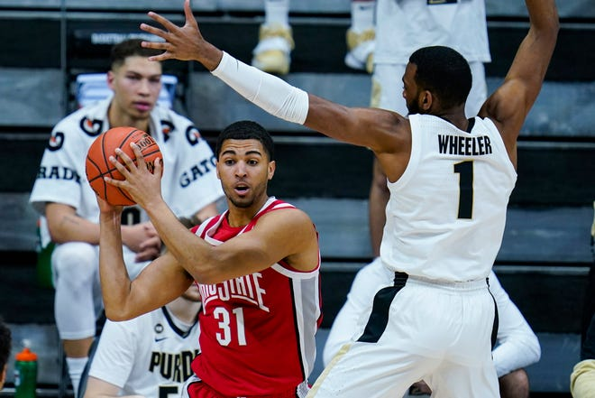 Ohio State forward Seth Towns (31) is pressured by Purdue forward Aaron Wheeler (1) in the second half of an NCAA college basketball game at the Big Ten Conference tournament in Indianapolis, Friday, March 12, 2021. Ohio State defeated Purdue 87-78 in overtime. (AP Photo/Michael Conroy)