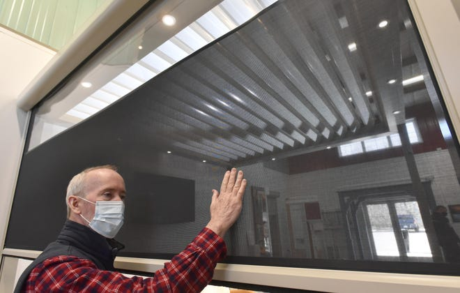 Paul Craig, founder and CEO of Shade & Shutter in Hyannis and Long Island, New York, demonstrates the strength of a roll-up screen material used to block the sun and wind in an unusual shutter system that is gaining popularity at homes and restaurants. STEVE HEASLIP/CAPE COD TIMES