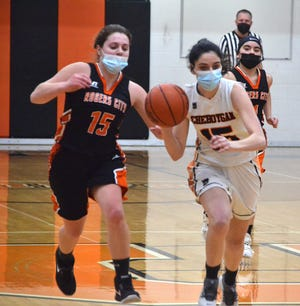 Cheboygan senior guard Kayla Burt (right) dribbles to the basket while Rogers City's Kaitlin Nowicki chases during the first quarter of a varsity girls basketball matchup in Cheboygan on Monday.