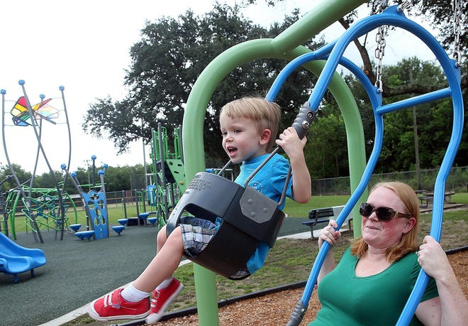 Brandy Coupel and her son Eli, 2, enjoy swinging in Schriever Park off Main Project Road in August 2018.