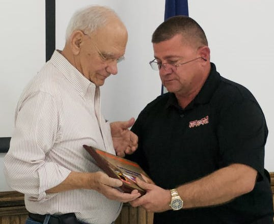 Terrebonne Parish Sheriff Tim Soignet presents Houma Toys for Tots organizer Linwood Liner with a plaque Saturday to thank him for his years of service.