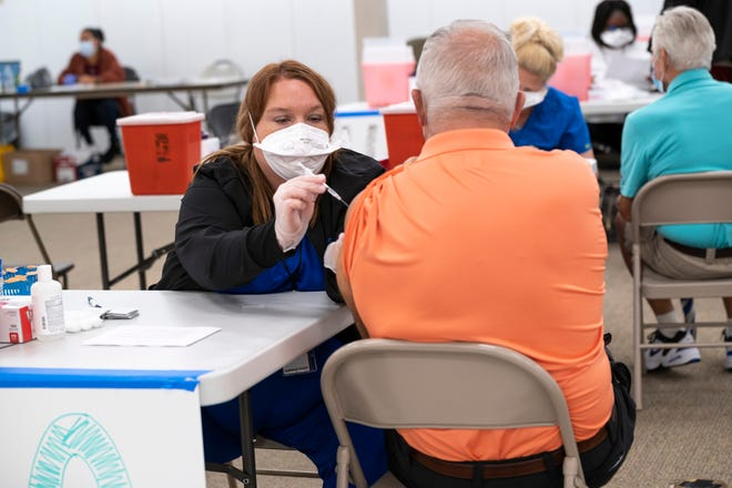 A health care worker administers a second round of the COVID vaccine at the Lake Square Mall in Leesburg. [Cindy Peterson/Correspondent]