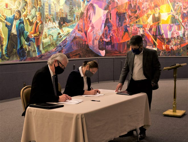 Malone University President David King (left) and Zollikon Institute Director Norita Yoder sign an agreement between the two institutions at the Amish and Mennonite Heritage Center in Berlin. Malone University Provost Greg Miller (right) looks on.