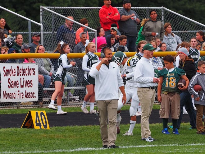 Sand Creek head football coach Marc Spicer walks the sidelines during a game as assistant coach.