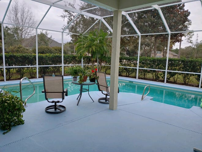 The pool area of this Breakaway Trails home is screened and has a covered patio.