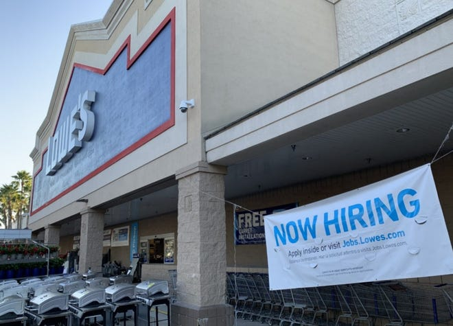 A hiring banner can be seen in front of the Lowe's Home Improvement store on Dunlawton Avenue in Port Orange on Saturday, Feb. 27, 2021.