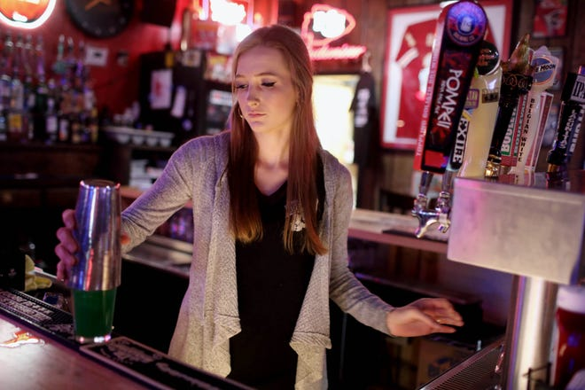 Chloe Armitage, head server and assistant general manager at The Buffalo Tavern, prepares a Shamrock cocktail, one of the tavern's St. Patrick's Day drink specials made with Malibu rum, Midori and Blue Curacao, Tuesday at 2016 S. Main St. in Burlington. The staff at The Buffalo Tavern, many whom will be working a double shift, are looking forward to a St. Patricks Day without closures or COVID-19 restrictions after Gov. Kim Reynolds shut down bars and other recreational facilities at noon on St. Patricks Day last year.