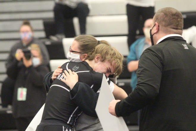 West Ottawa's Mathew Hakken hugs his mother after winning his 100th career match