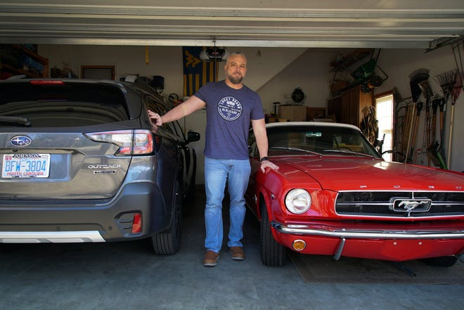 Steve Bock stands between his new Subaru Outback and his 1965 Ford Mustang at his home in Apex on Friday, March 5, 2021. He would like to have an electric car, but says the prices will have to come down a lot before he can do it. Opinion polls show that most Americans would consider an EV if it cost less, if more charging stations existed and if a wider variety of models were available. (AP Photo/Allen G. Breed)