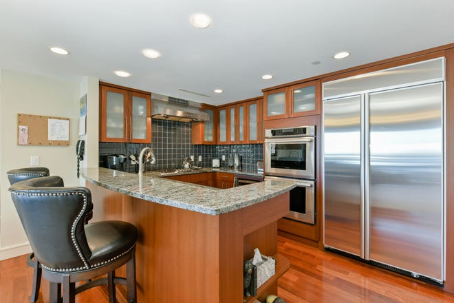 The openness continues into the granite chef's kitchen where the warmth of wood cabinetry, the earthiness of gray granite counters, the serenity of hunter-green tile backsplashes and the shine of stainless Thermador appliances reflecting the window light concoct a tasteful potpourri of finishes.