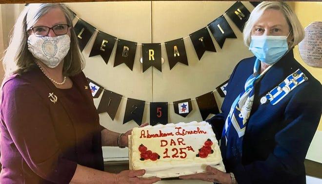 Marge Aper, left, shares a cake with DAR director Susan Beard.