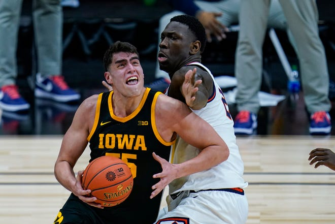 Illinois center Kofi Cockburn, right, defends against Iowa center Luka Garza (55) in the first half of an NCAA college basketball game at the Big Ten Conference tournament in Indianapolis, Saturday, March 13, 2021.