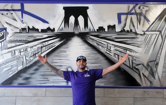 Neko Salameh stands in front of artwork in his new Neko's of New York location in the Old Path Village Shopping Center in Framingham on March 16, 2021.
