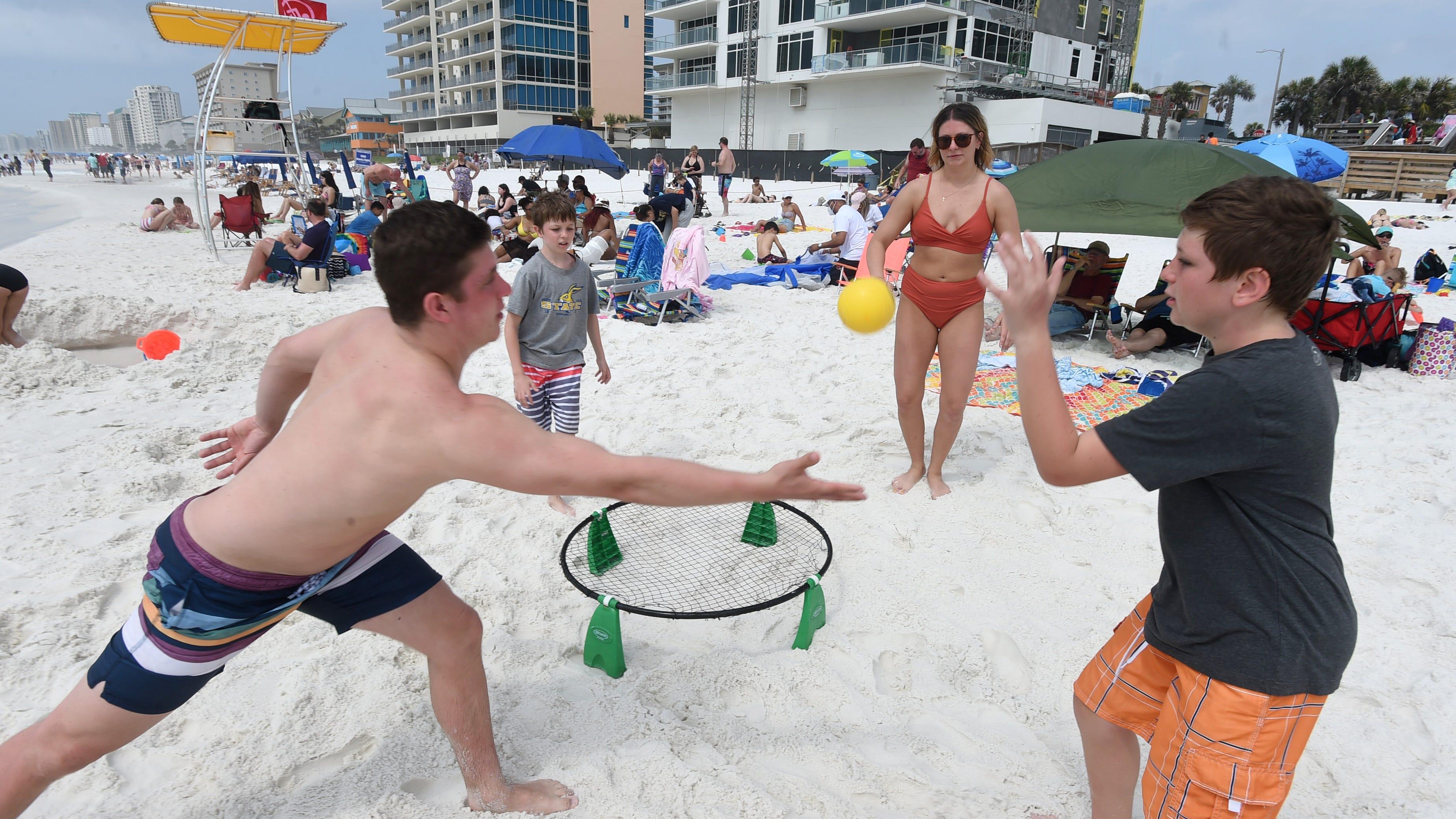 El martes por la tarde, Kale Stevenson, a la izquierda, se lanza para un tiro mientras juega con los hermanos (de izquierda a derecha) Kobe, Ellie y Deek en la playa de Tests.  El fuerte oleaje del martes se refiere a nadar en las playas de la isla de Oculus y debería estar cerca de la orilla de la Prueba.