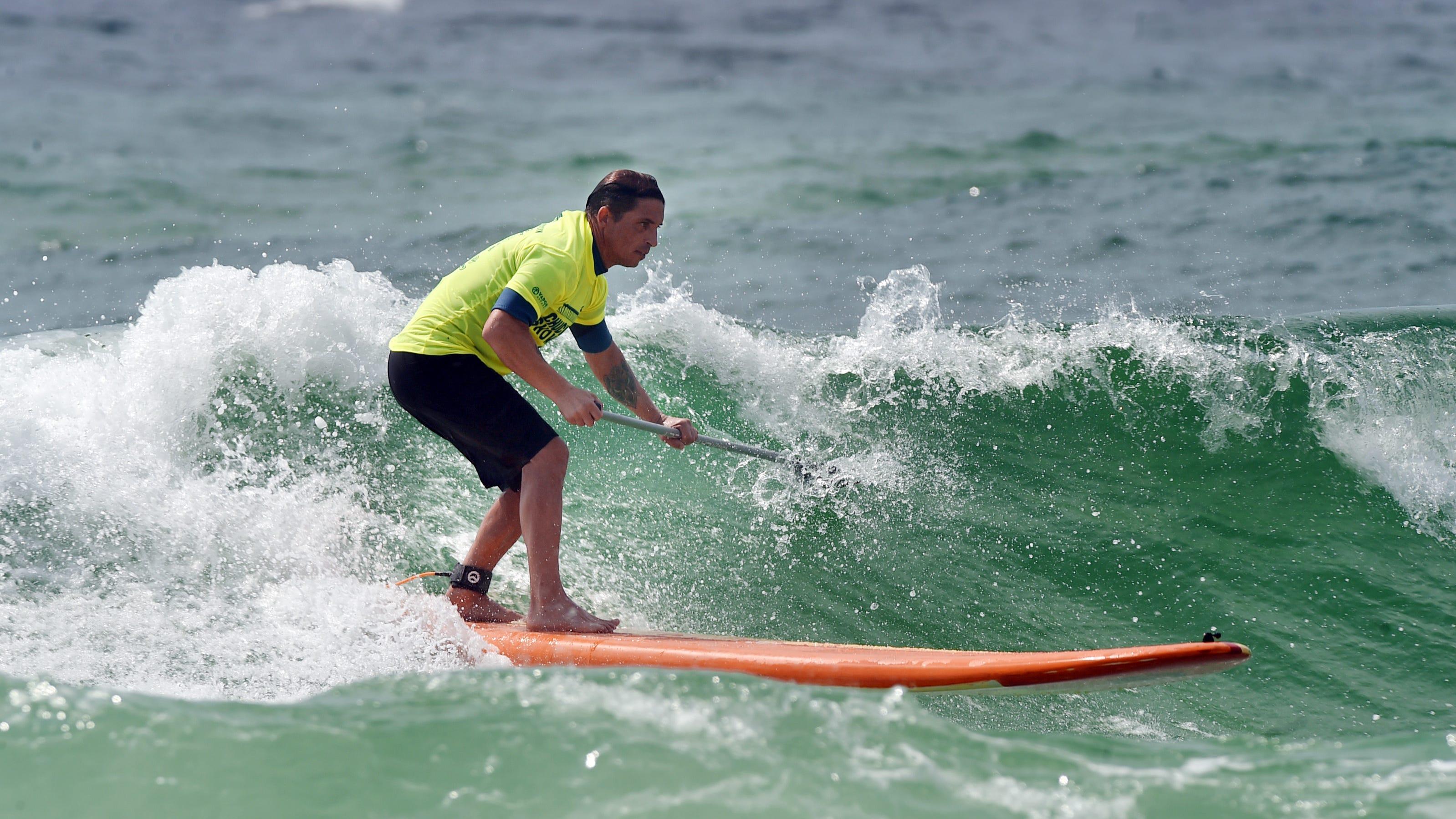 Shane Sehul navega con su remo en una ola cerca de la playa en Tests el martes.  El martes, los surfistas duros mantuvieron a los nadadores frente a la costa de la isla de Oklahoma y Testin cerca de la costa.