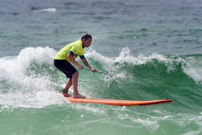 Shane Sehul navega con su remo en una ola cerca de la playa en Tests el martes.  Los surfistas rudos mantuvieron a los nadadores frente a la costa de la isla de Oklahoma y Testin cerca de la costa.