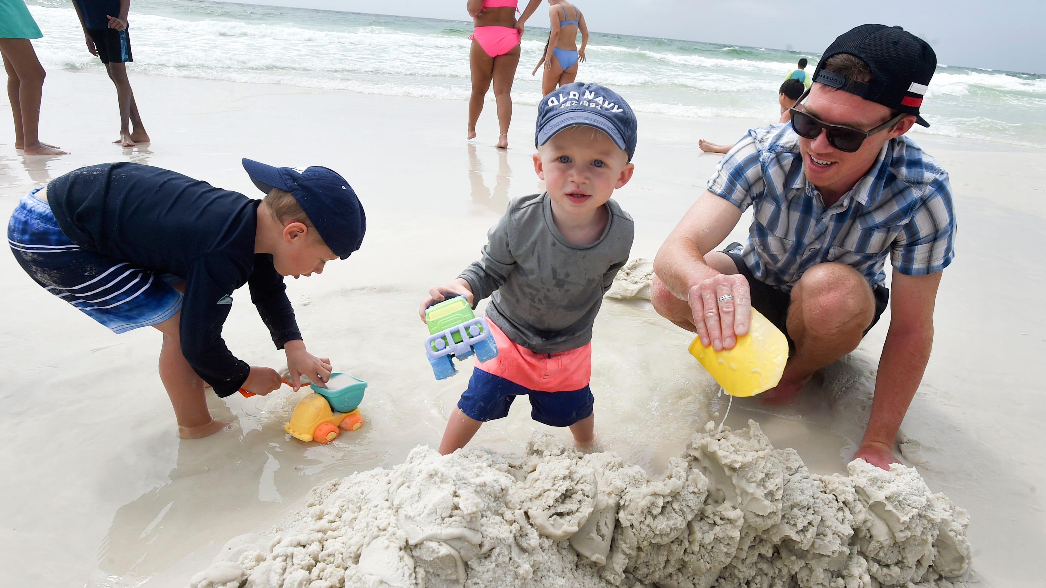 Patrick McCombs está trabajando con sus hijos Campbell, a la izquierda, y Cotton en una duna de arena en la playa en Tests el martes por la tarde.  El martes, los surfistas duros mantuvieron a los nadadores frente a la costa de la isla de Oklahoma y Testin cerca de la costa.