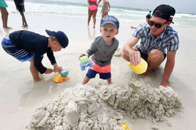 Patrick McCombs está trabajando con sus hijos Campbell, a la izquierda, y Cotton en una duna de arena en la playa en Tests el martes por la tarde.  El martes, surfistas rudos mantuvieron a los nadadores frente a la costa de la isla de Oklahoma y Testin cerca de la costa.