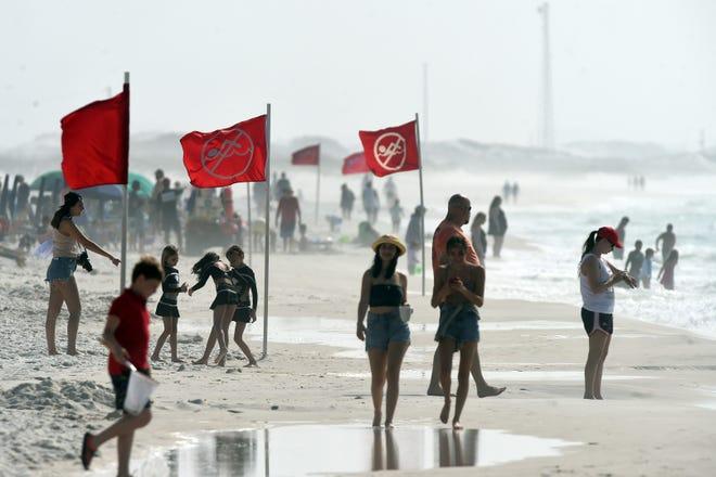 Varias banderas de advertencia se colocaron en la isla de Oculus el martes por la mañana para advertir a los nadadores de las amenazas actuales.  El martes, los rudos surfistas mantuvieron a los nadadores varados frente a la costa de la isla de Oculus y Destiny.