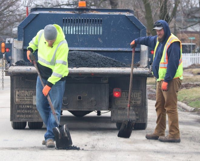 Kevin Dirks fills a pot hole while colleague Zach Van Winsen watches. The City of Pontiac employees spent a portion of their afternoon filling pot holes on Water Street.