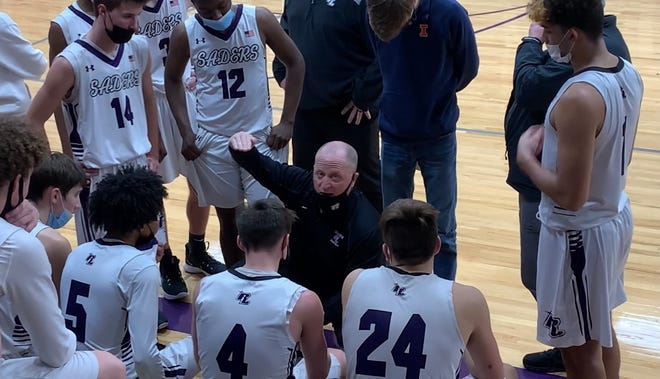 """Lutheran head coach Tom Guse talks to senior point guard Zach Derus (4) and the rest of the Crusaders during a win this season. Guse and Derus, who led Lutheran to a perfect 16-0 record this season, are two of the guests on this week's podcast """"Not Just a Game."""""""