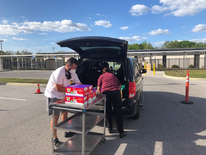 Volunteers from All Faiths Food Bank help to distribute meals on March 12 at Fruitville Elementary School in Sarasota County in advance of spring break.