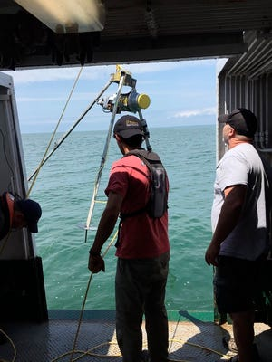 This undated photo provided by Josef Daniel Ackerman of the University of Guelph, in Guelph, Ontario, Canada, shows researchers aboard the research vessel Keenosay deploying scientific instruments in Lake Erie. Powerful gusts linked to global warming are damaging water quality and creating a hazard for fish in Lake Erie and perhaps elsewhere in the Great Lakes, according to researchers. (Aidin Jabbari/University of Guelph via AP)