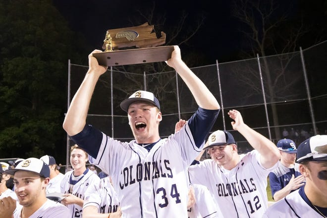 Shrewsbury's John West hoists the Division 1 Central baseball championship trophy in 2019.