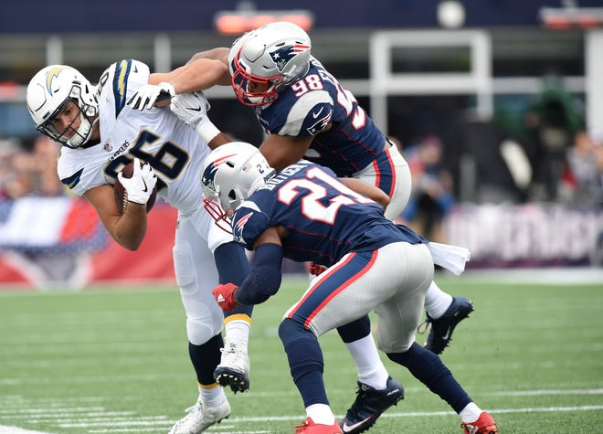Chargers tight end Hunter Henry  holds onto the ball after getting knocked out of bounds by Patriots cornerback Malcolm Butler (21) and defensive end Trey Flowers during a game in 2017 at Gillette Stadium.