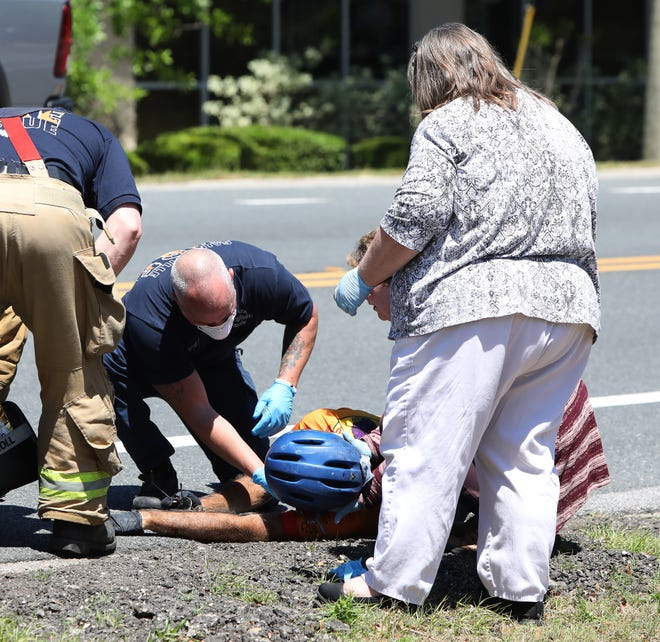 A first responder with Gainesville Fire Rescue and two passersby work to help a bicyclist hit by a car on Northwest 34th Street near the Pinch A Penny in Gainesville on April 2.