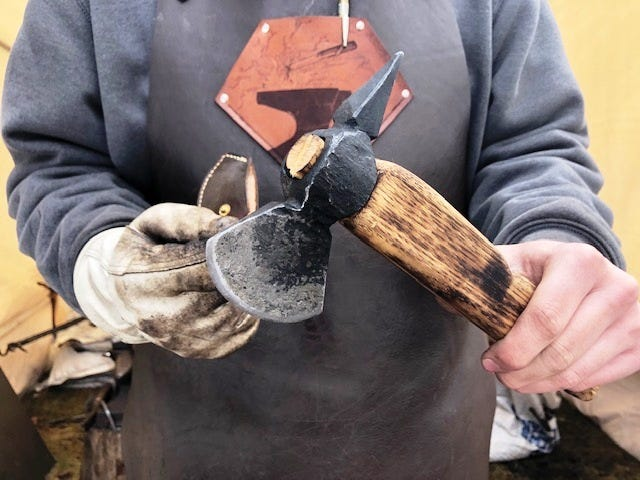 Nicholas Riolo, 17, of Bellingham, shows a hatchet he crafted in his backyard forge. The hatchet head is affixed to an antique wooden handle.