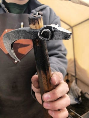 Nicholas Riolo, 17, of Bellingham, shows a tool with a ram's head he crafted for himself, created from a railroad spike and an antique wooden handle.