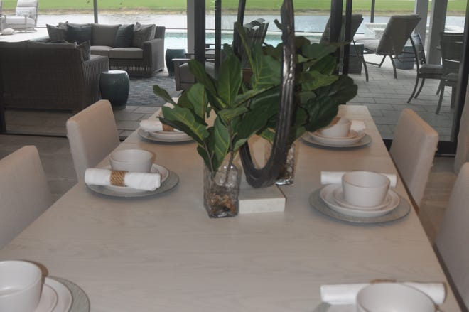 The dining room table stretches toward the lanai where more seating is available for outdoor dining.