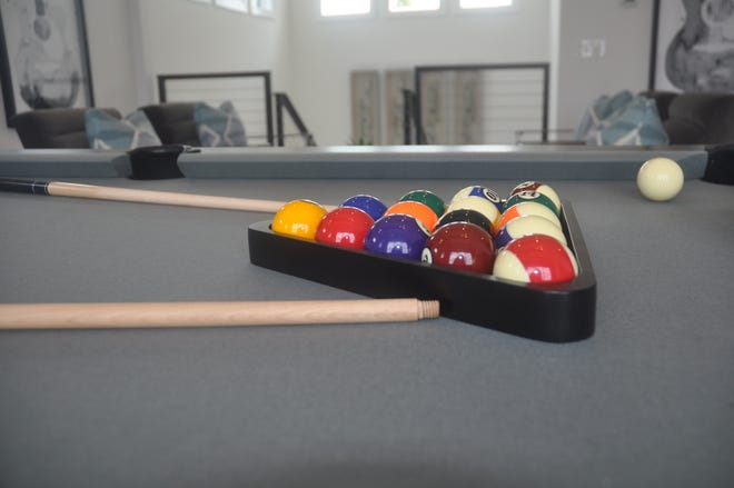 The loft features a billiards table, sitting area, mini refrigerator and sliding glass doors that lead to an upstairs terrace.