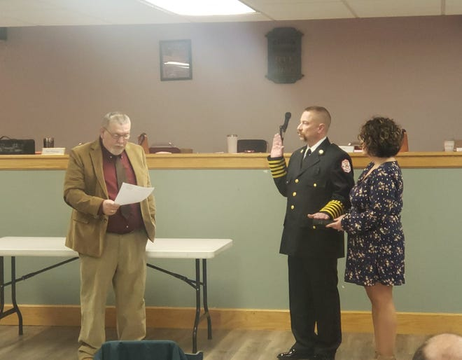 Madison Township Trustees Chairman James Hauser swears in Kenneth Justus as the township's new fire chief.