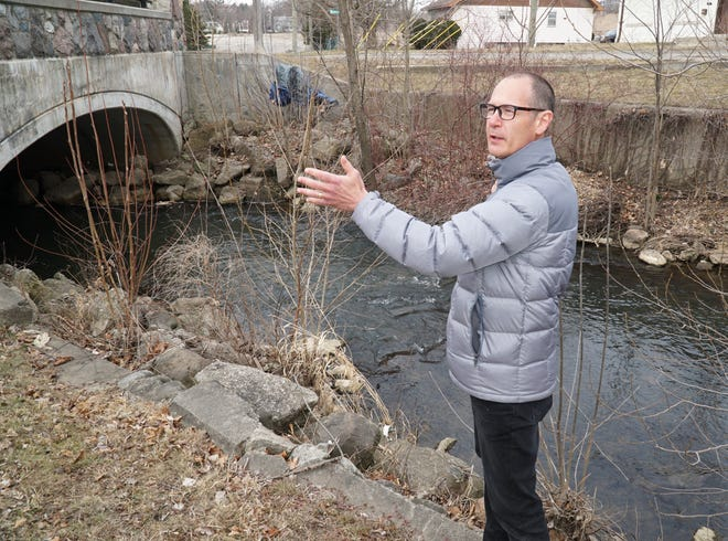 Marty Boote, an environmentalist for ARC, stands near the bridge to the east of Northville Downs where the Rouge River begins its journey underneath the race track.  Boote is part of the team that is trying to see if they can 'daylight' the section of river that has long been hidden in this underground tunnel.