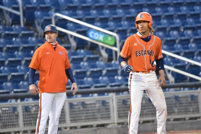 Escambia High's JoJo Blackmon takes lead off third base ahead of Gators head coach Tracey King  in a game at Blue Wahoos Stadium on March 16, 2021.