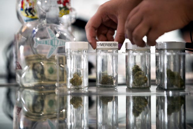 Marijuana flower is seen in glass jars on opening day at Mint Dispensary on Cave Creek Road in Phoenix on March 15, 2021. Mint sells both medical and recreational marijuana and products.