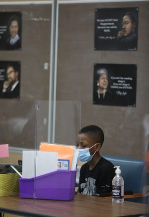 Jhaydin McNair, in sixth grade, looks at his laptop at Dr. Charles T. Lunsford School 19 in Rochester, NY on March 16, 2021.  Because of COVID precautions, students have their own laptop and are seated with one other student with a see through barrier separating the two.